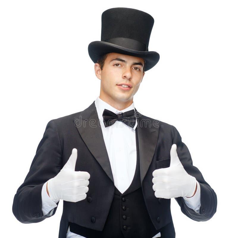 Magicien dans le chapeau supérieur montrant des pouces  photo libre de droits
