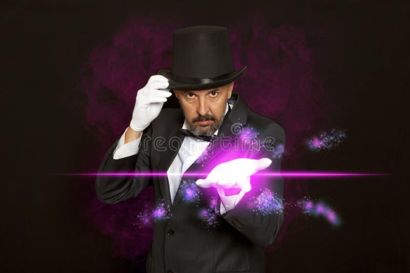 Magicien dans le tour d'apparence de chapeau supérieur sur le noir photo stock