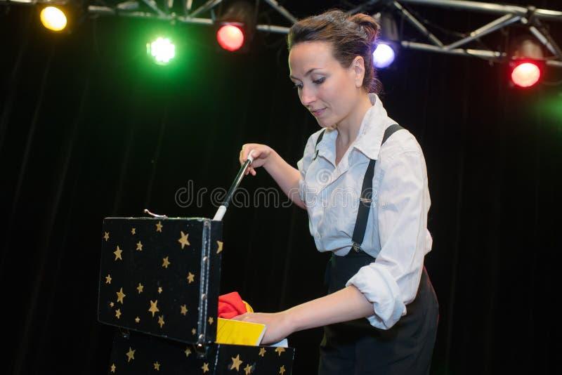 Magicien de femme faisant des tours avec la baguette magique photos stock