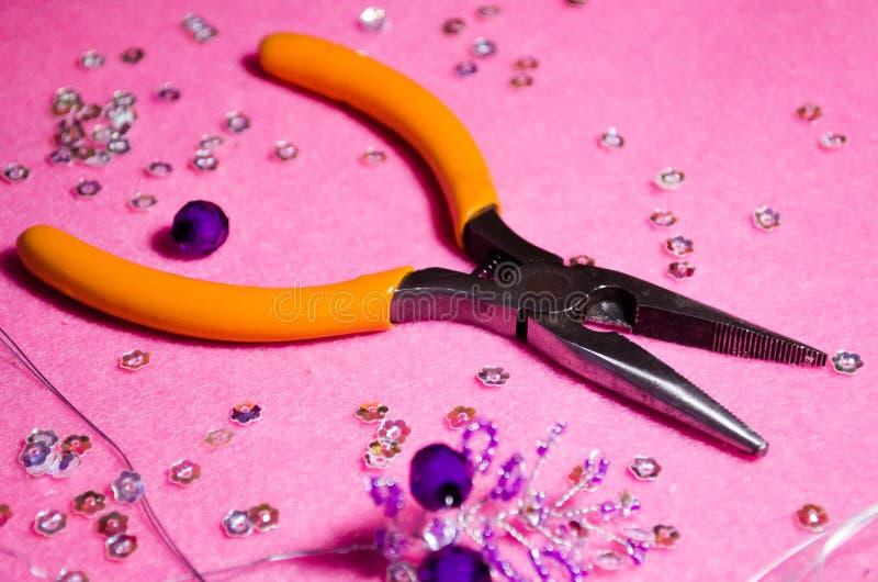 Magicien de pinces Pinces pour des décorations Le processus de créer des bijoux beads Classe principale Un brin des perles Maître images stock