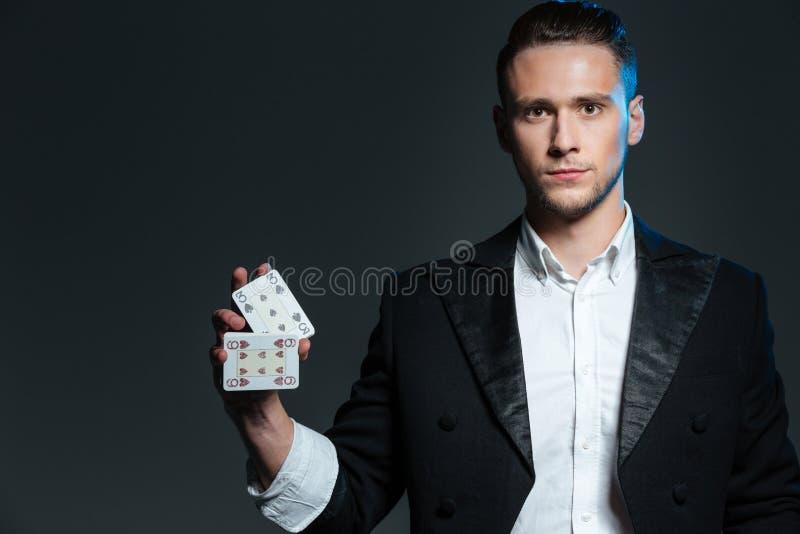 Magicien sérieux de jeune homme tenant et tenant deux cartes jouantes photos stock