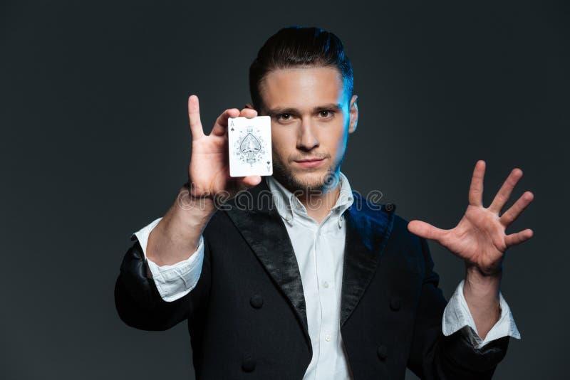 Magicien sûr de jeune homme montrant la carte d'as images stock