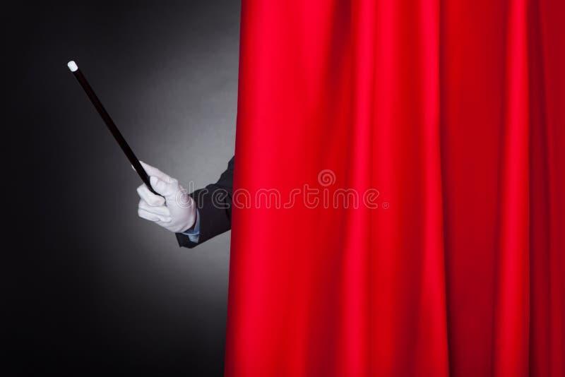 Magicien tenant la baguette magique derrière le rideau en étape images stock