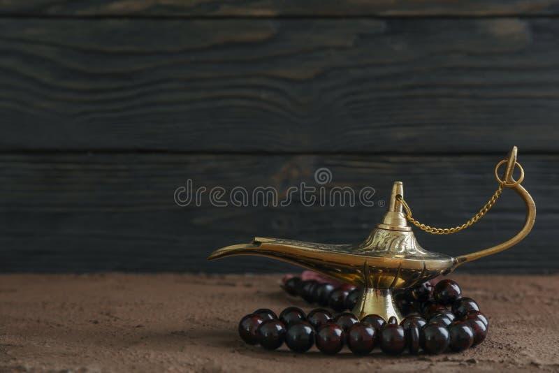 Magiczna Aladdin lampa z modlitewnymi koralikami na brązu stole obraz royalty free