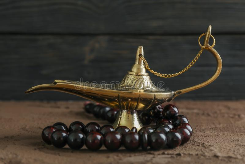 Magiczna Aladdin lampa z modlitewnymi koralikami na brązu stole fotografia stock