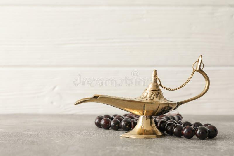 Magiczna Aladdin lampa z modlitewnymi koralikami na popielatym stole zdjęcia stock