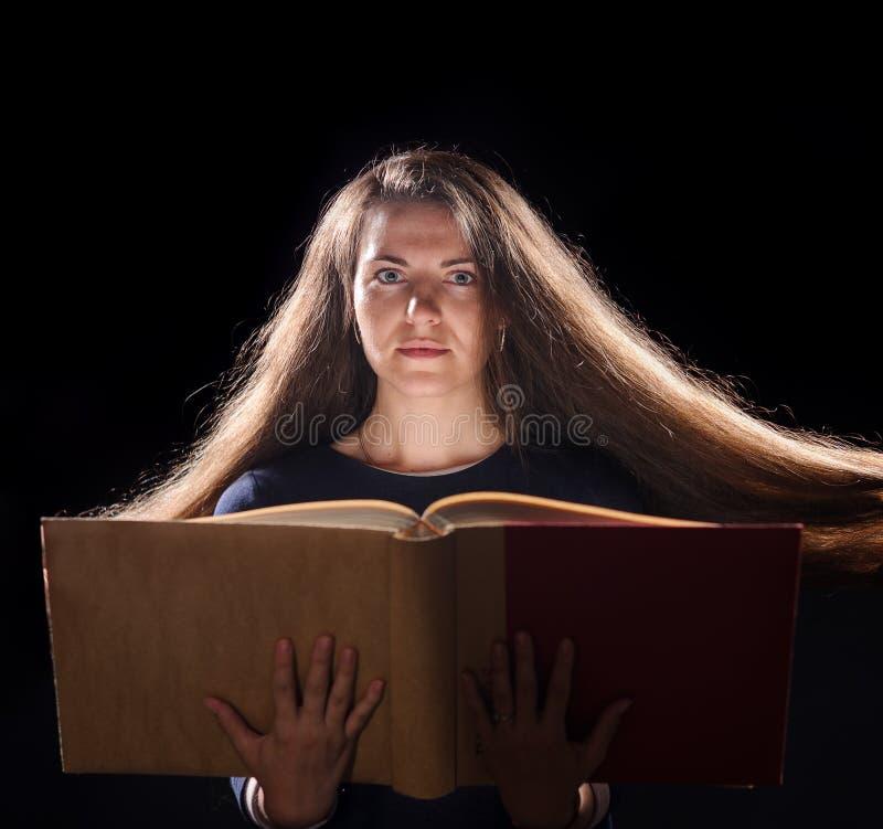 Magiczna kobieta czyta książkę Czarny t?o obraz royalty free