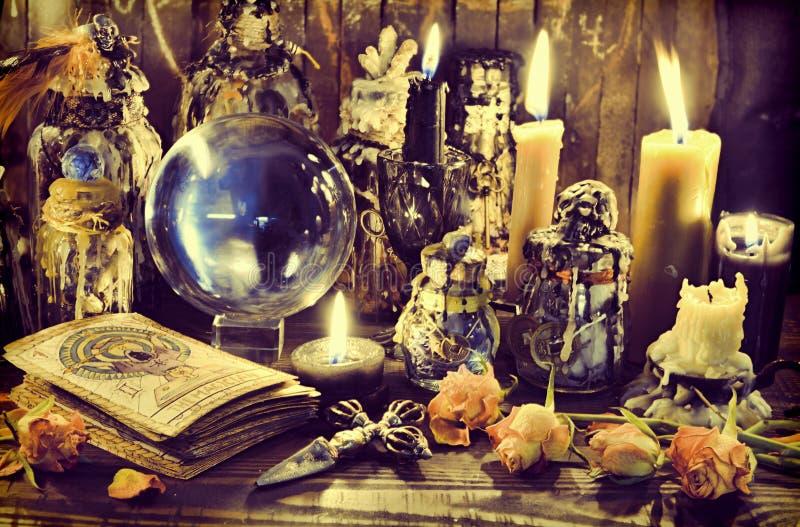 Magiczna kryształowa kula, czarownic butelki i płonące świeczki na drewnianym stole, obraz stock