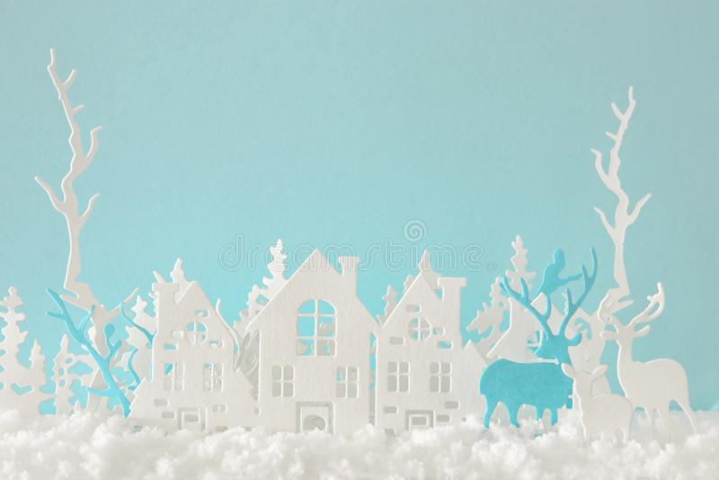 Magicznego boże narodzenie papieru zimy tła rżnięty krajobraz z domami, drzewami, rogaczem i śniegiem przed pastelowym błękitnym  royalty ilustracja