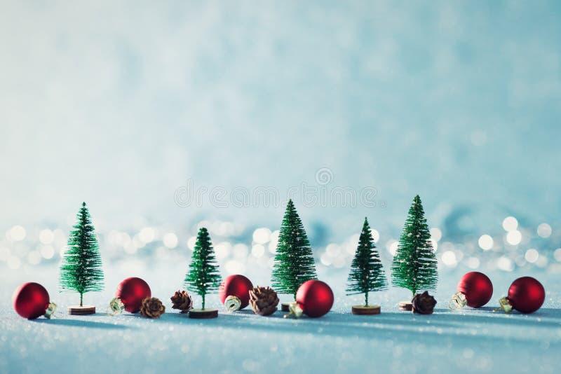 Magiczny miniaturowy zimy kraina cudów tło Wiecznozieloni drzewa, sosna rożki i czerwoni bożych narodzeń baubles na błyszczącym b zdjęcia royalty free