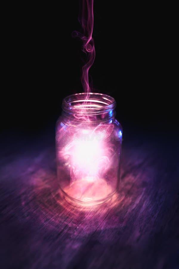 Magie in einem Glas auf einem dunklen Hintergrund stockfotografie
