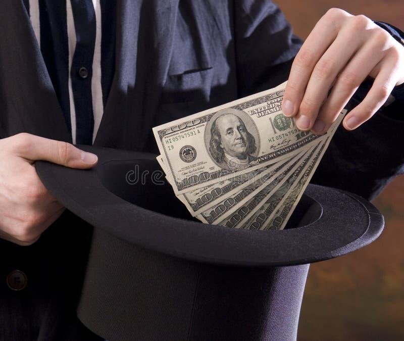 Magier, der Geld vom tophat zieht lizenzfreie stockfotografie
