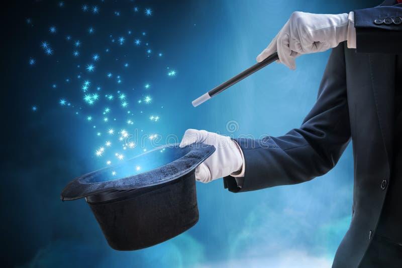 Magier oder Zauberkünstler zeigt Zaubertrick Blaues Stadiumslicht im Hintergrund lizenzfreie stockfotos