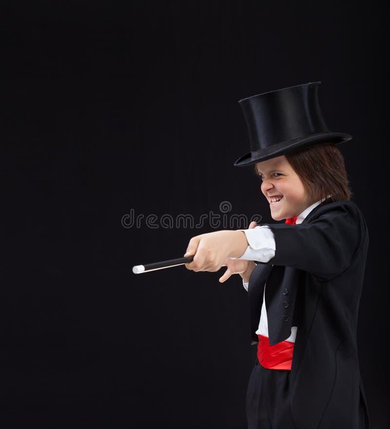 Magierjunge mit Hardhat zeigend auf Kopienraum mit magischem Stab lizenzfreie stockbilder