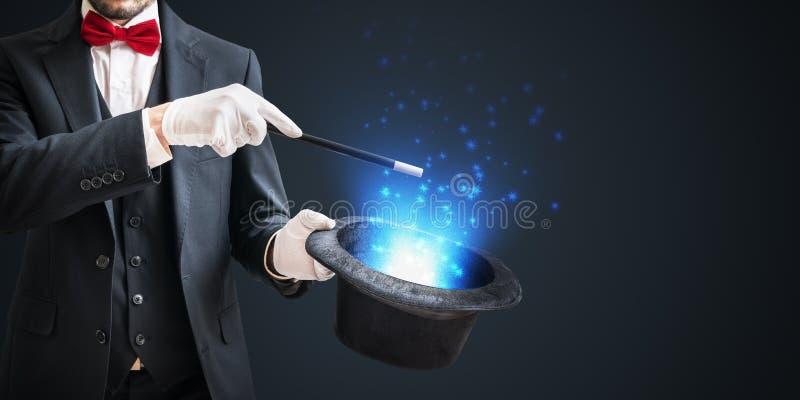 Magik lub iluzjonista pokazujemy magiczną sztuczkę z różdżką i kapeluszem na ciemnym tle fotografia royalty free