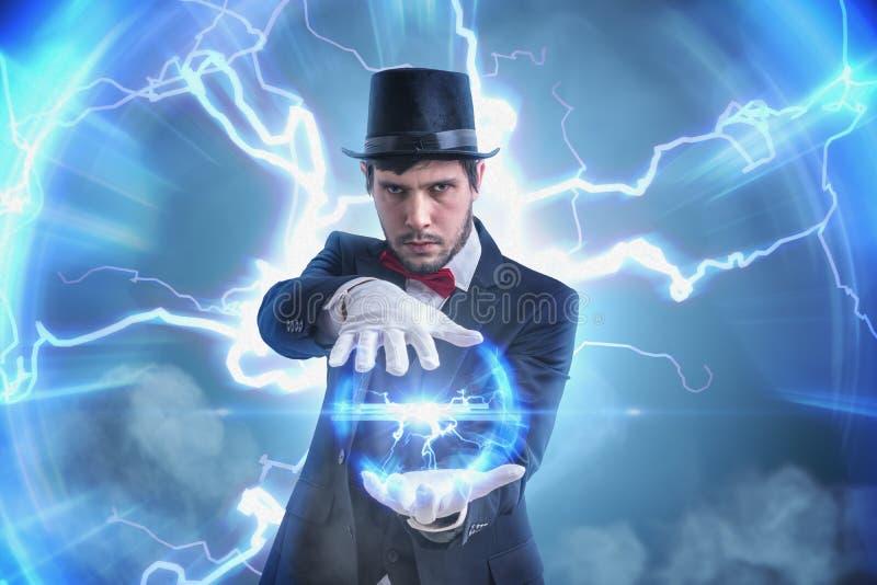 Magik lub iluzjonista promieniuje jaskrawego światło trzymamy elektryczną osocze piłkę Błyskawica w tle zdjęcie stock