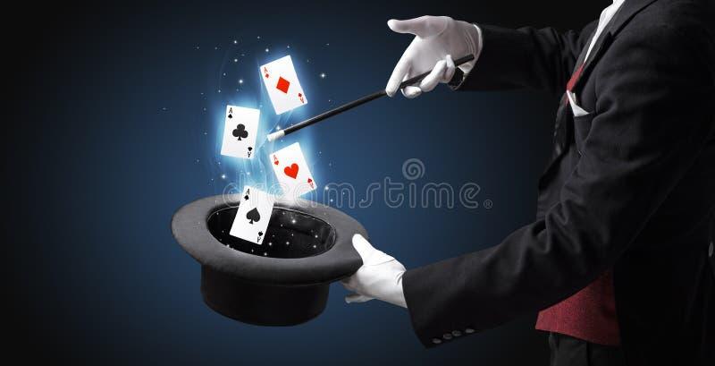 Magik robi sztuczce z różdżką i karta do gry zdjęcia royalty free