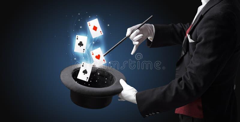 Magik robi sztuczce z różdżką i karta do gry fotografia royalty free