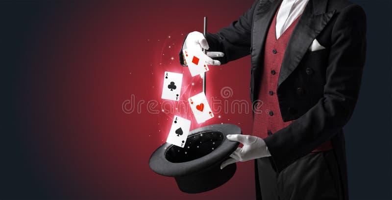 Magik robi sztuczce z różdżką i karta do gry fotografia stock