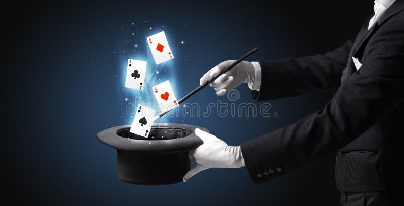 Magik robi sztuczce z różdżką i karta do gry zdjęcie stock