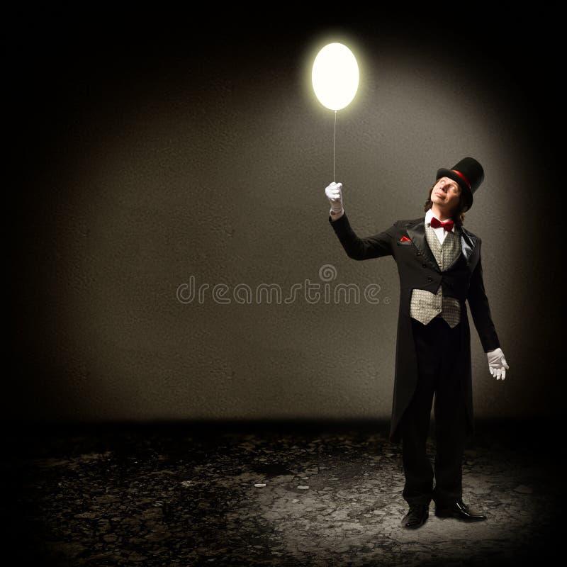 Magik trzyma rozjarzonego balon obraz royalty free