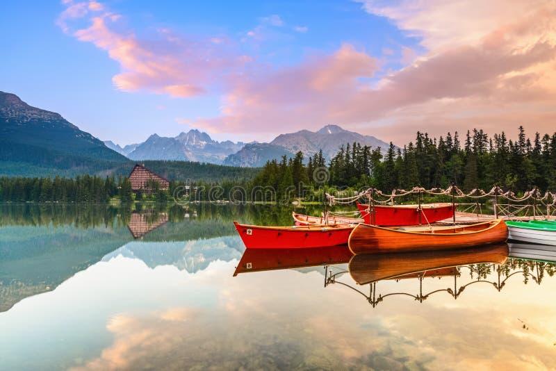 Magisch meer met rode boten en kano stock afbeelding