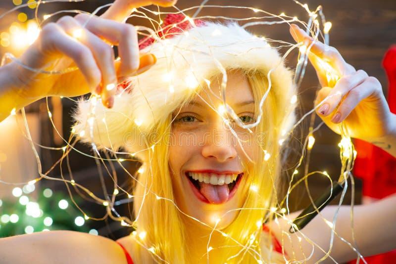 Magisch Ogenblik Liefdevrede en vreugde voor geheel jaar De hoed van meisjessanta thuis dichtbij Kerstmisboom Het sexy meisje vie stock fotografie