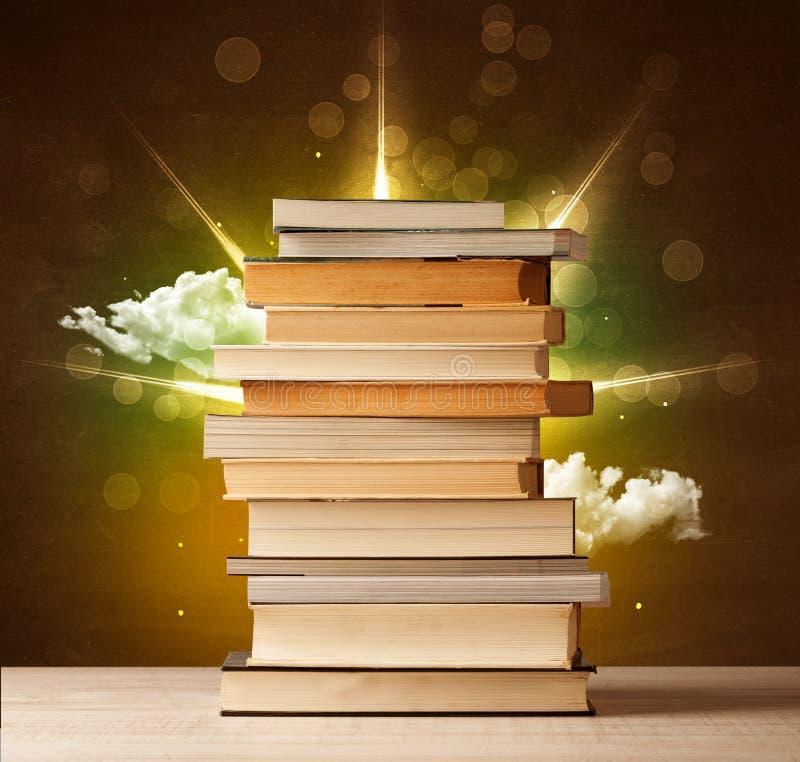 Magische Bücher mit Strahl von magischen Lichtern und von bunten Wolken vektor abbildung