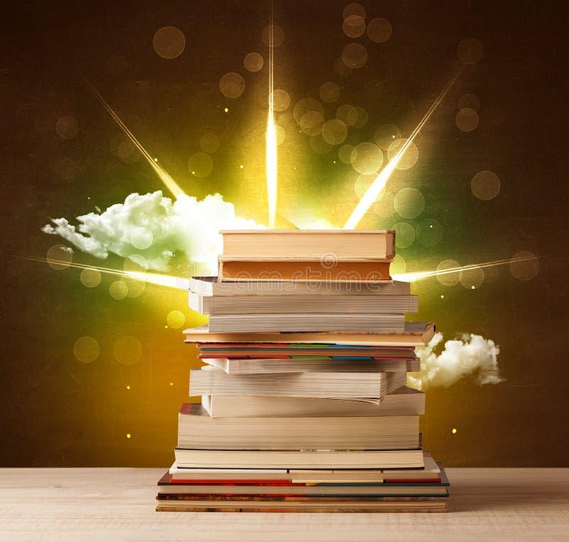 Magische Bücher mit Strahl von magischen Lichtern und von bunten Wolken stock abbildung
