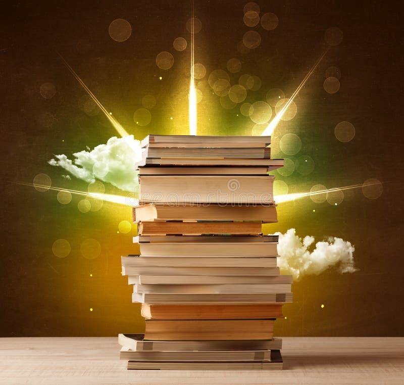 Magische Bücher mit Strahl von magischen Lichtern und von bunten Wolken lizenzfreie abbildung