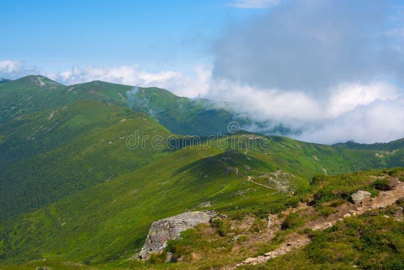 Magische Berglandschaft - Wolken schwimmt über grüne Kanten lizenzfreie stockfotos