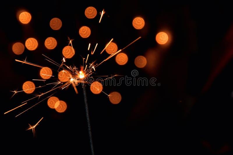 Magische brennende Wunderkerze Dunkler Hintergrund mit unscharfen Lichtern der Weihnachtsgirlande Kopieren Sie Platz auf dem Rech lizenzfreies stockbild