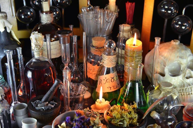 Magische Flaschen und brennende Kerzen auf Hexentabelle stockbilder