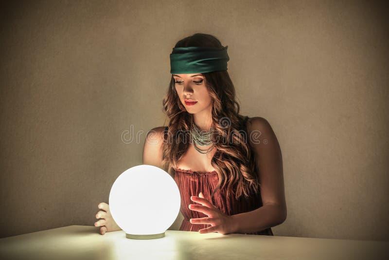 Magische Frau, die eine Glaskugel betrachtet lizenzfreie stockbilder