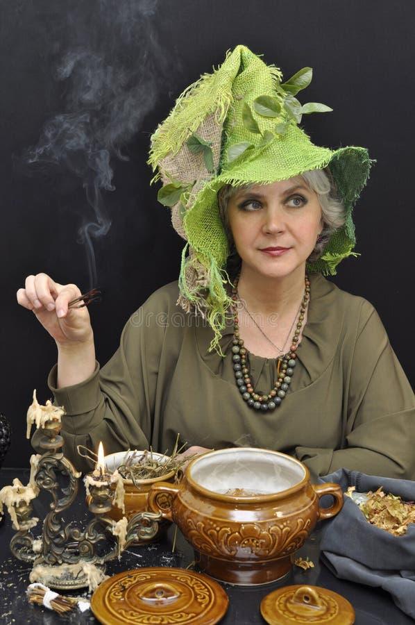 Magische Frau im grünen Hut mit den rauchenden Zweigen stockfoto