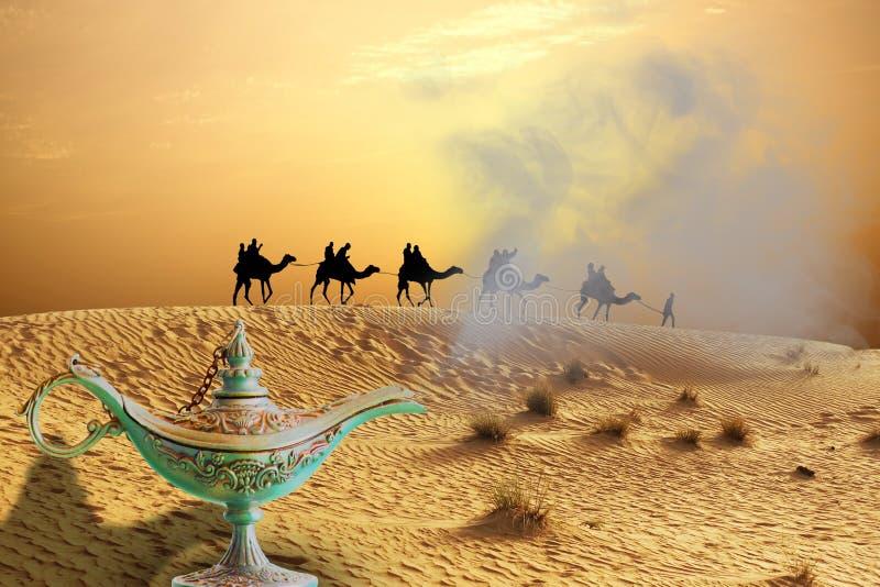 Magische genielamp op zandduinen met de caravan die van de kameelrit in Arabische Woestijn reizen stock fotografie