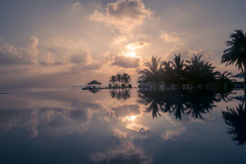 Magische gouden die zonsondergang met wolken op een strand in de Maldiven, in een oneindigheidspool wordt weerspiegeld royalty-vrije stock foto