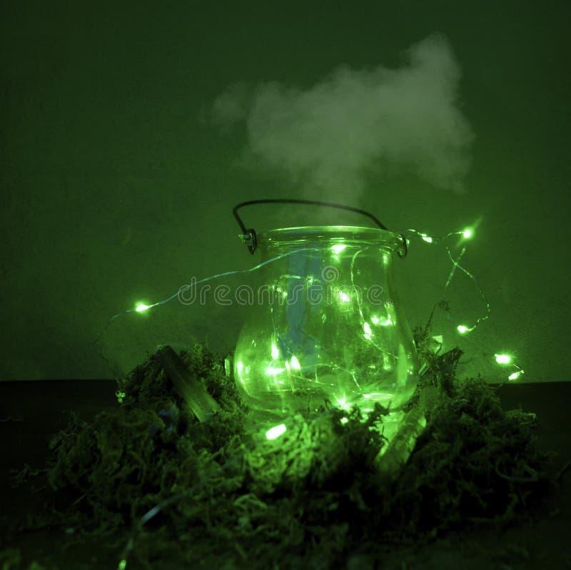 Magische ketel op groene achtergrond met mos en glimworm en mist en rook en bokeh royalty-vrije stock afbeeldingen