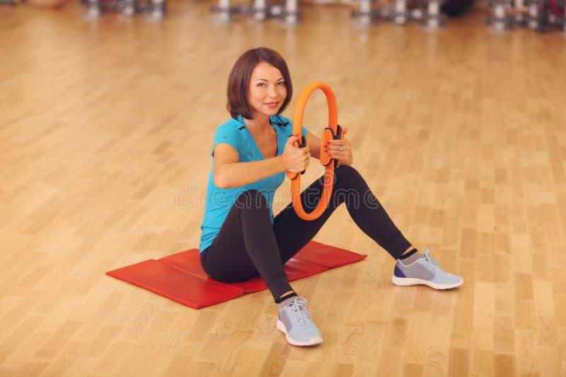 Magische pilates bellen de oefeningen van de de sportgymnastiek van de vrouwenaerobics op de vloer die, die en aan camera glimlac royalty-vrije stock afbeelding