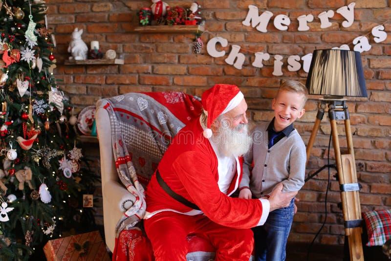 Magische Santa Claus en weinig jongen het voor de gek houden rond en hebben pret tog stock afbeeldingen