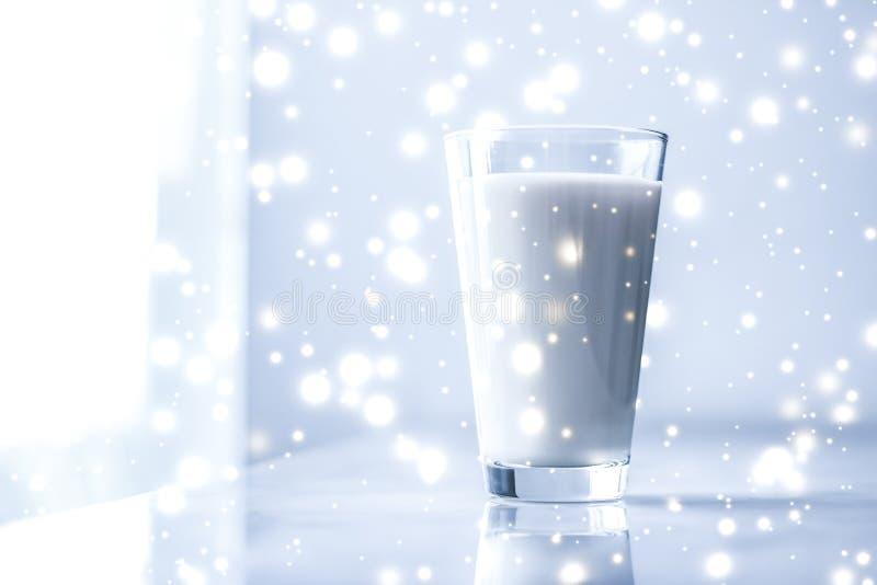Magische vakantiedrank, gietende organische lactose vrije melk in glas op marmeren lijst stock foto
