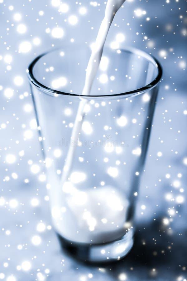 Magische vakantiedrank, gietende organische lactose vrije melk in glas op marmeren lijst stock foto's