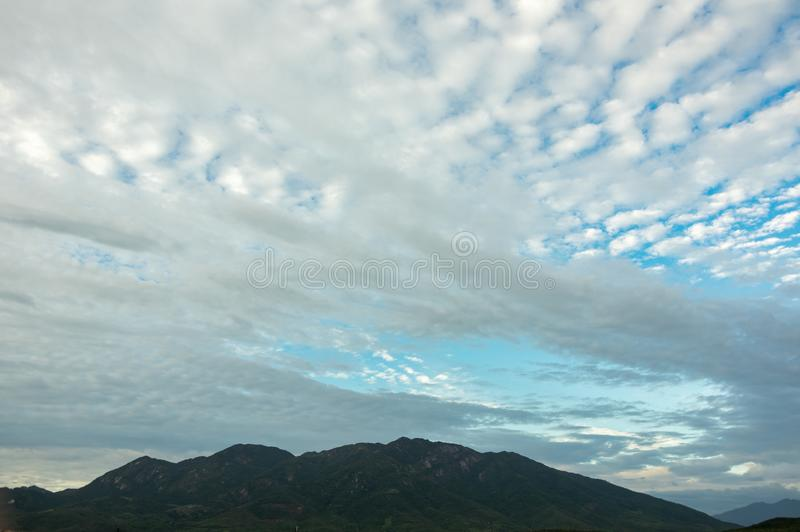 Magischer Himmel und Wolken mit Bergen am Morgen lizenzfreie stockfotos