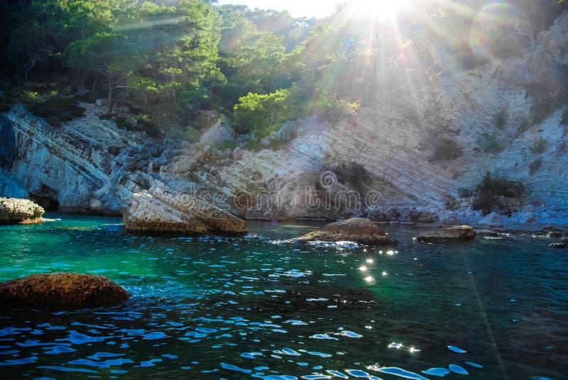 Magischer Sonnenschein durch die Berge in der blauen Bucht im Mittelmeer lizenzfreie stockbilder
