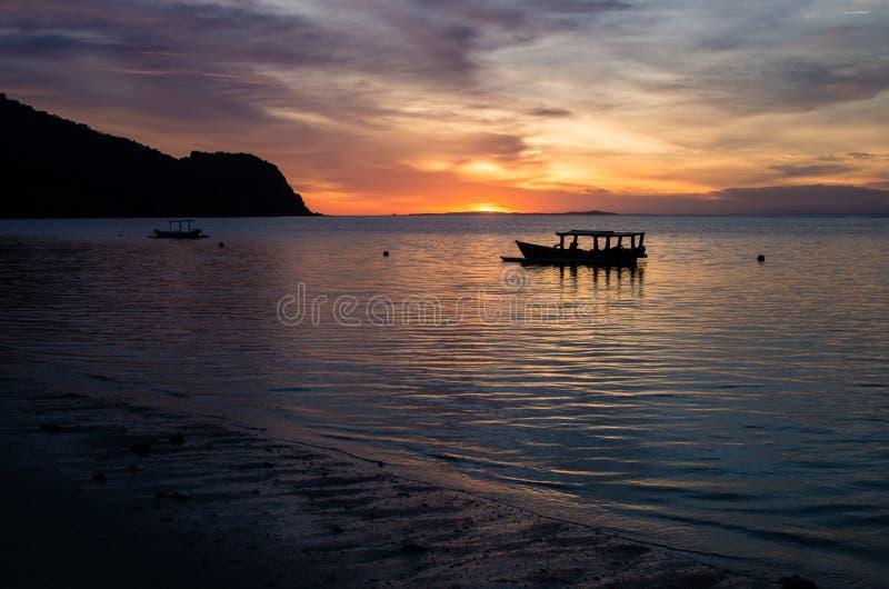 Magischer Sonnenuntergang mit traditionellem Boot an einem einsamen Strand nahe Brandungsstellen-Narbenriff auf Sumbawa, Indonesi stockfoto