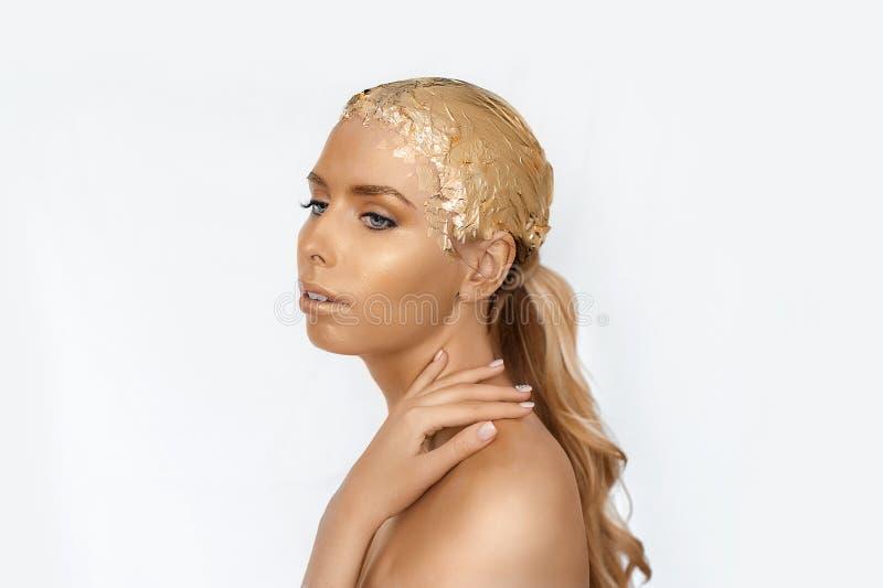 Magisches Mädchenporträt mit Goldhaut Goldenes kreatives Make-up, Nahaufnahmeporträt in der Atelieraufnahme, Farbe stockfotos