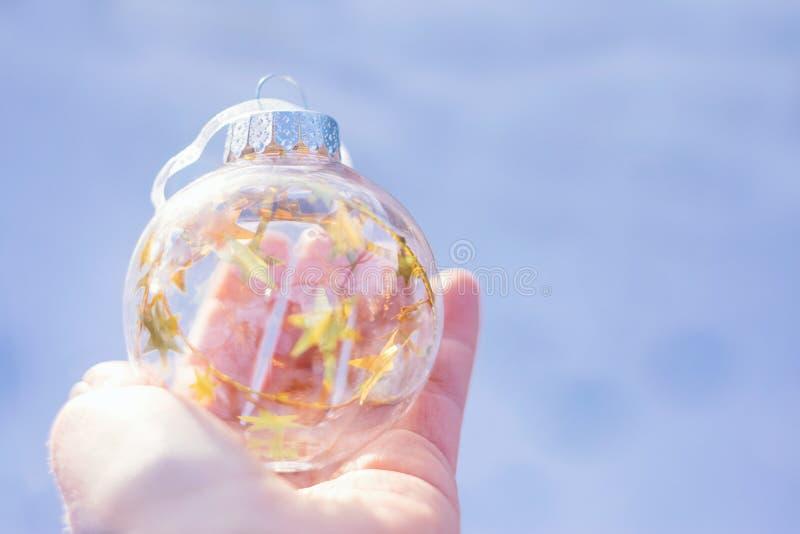 Magisk boll för jul som väntar på julen, magisk atmosfär Genomskinlig exponeringsglasjulboll med guld- stjärnor i kvinnlig royaltyfri foto