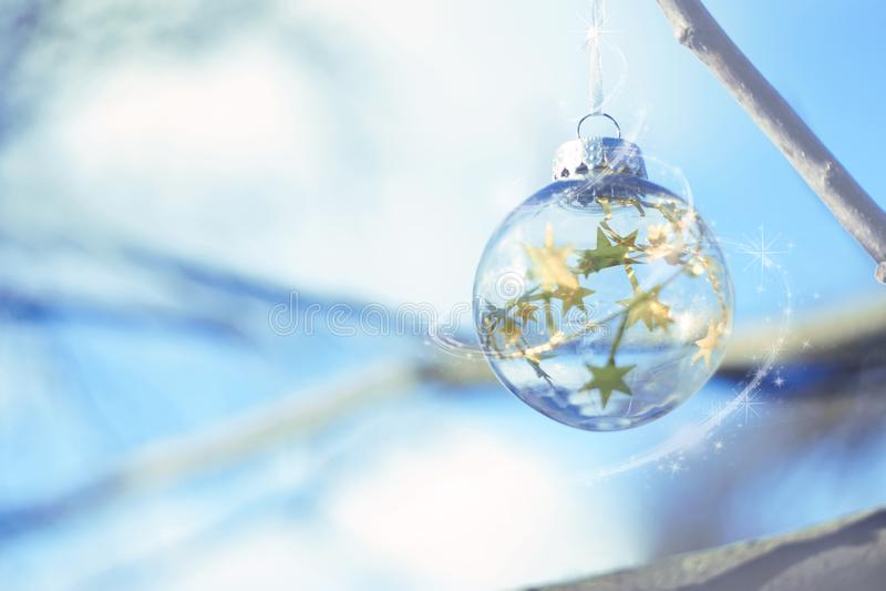 Magisk boll för jul, väntande på jul, magisk atmosfär Genomskinlig exponeringsglasjulboll med ljus och stjärnor i blå himmel royaltyfri foto