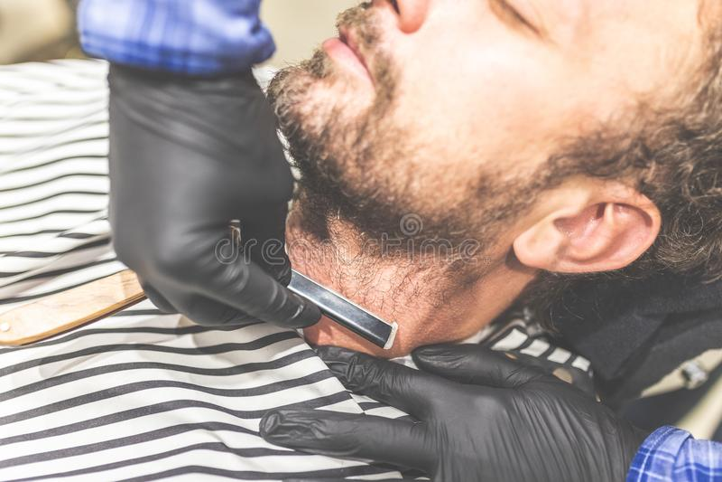 Magisk danandeh?rblick Närbildsidosikt av den unga skäggiga mannen som får rakad med den raka kantrakkniven av frisören på arkivfoto