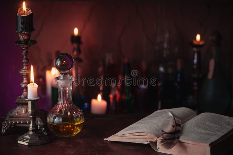 Magisk dryck, forntida böcker och stearinljus arkivbild
